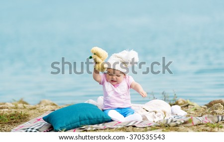 The little girl sits on a cover at the river and is capricious. - stock photo