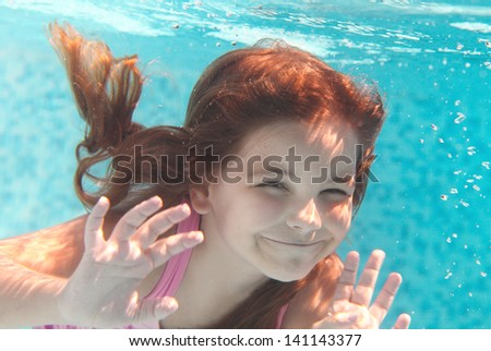 The little girl swimming underwater and smiling. Shot was taken with waterproof box - stock photo