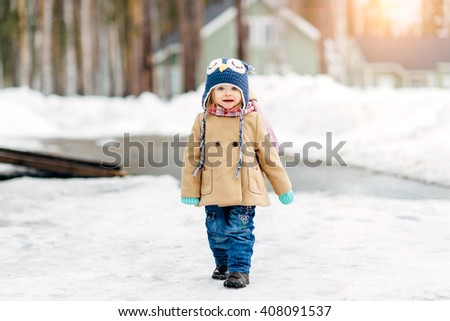 the little girl walks in the winter outdoors - stock photo