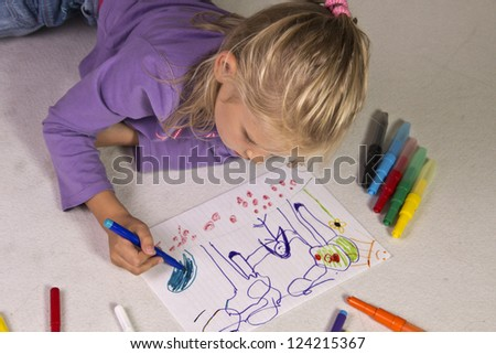 The little girl with blond hair draws - stock photo