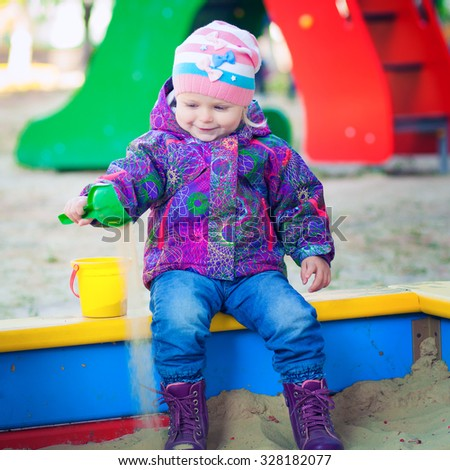 The little kid playing toys in sand. cute little girl in a sandbox in cold weather - stock photo