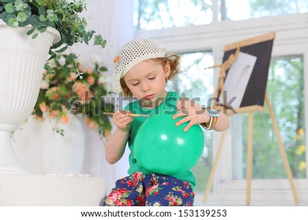 The little painter paints pictures on a green balloon - stock photo