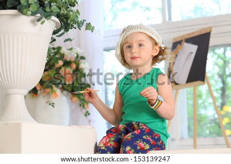 The little painter with brush in hand - stock photo