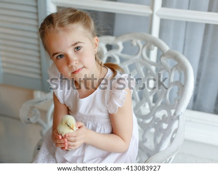 The little red-haired girl with pigtails holding a yellow chick, on a light background - stock photo