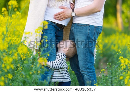The little son holds a leg of the mother. Mother is pregnant. On a photo legs of parents are shown. - stock photo