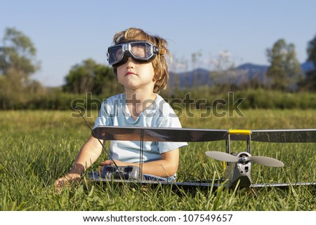 The little villain kid and his new RC plane, outdoors on grass - stock photo