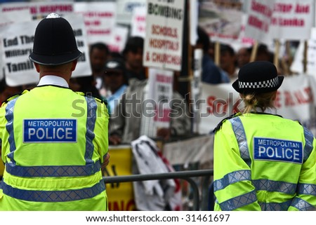 The London Metropolitan Police Force watching as a protest takes place in the street. - stock photo
