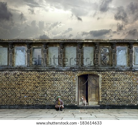 The lonely boy with a dog before an old brick wall - stock photo