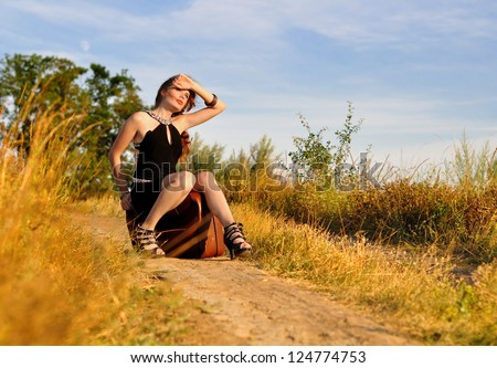 The lonely girl sit on old suitcase - stock photo