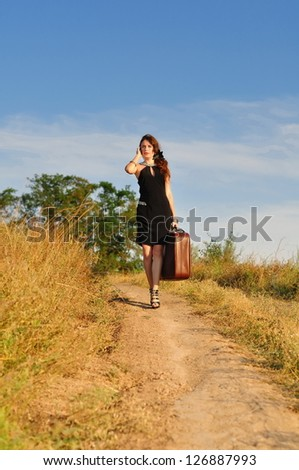 The lonely girl with an old suitcase goes on the rural road - stock photo