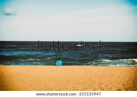 The lonely man on the beach Barcelona, one thinks at the shore of the ocean - stock photo
