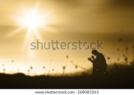 The lonely man. People kneeling and praying over blurred the white cross on golden light sunset background. - stock photo