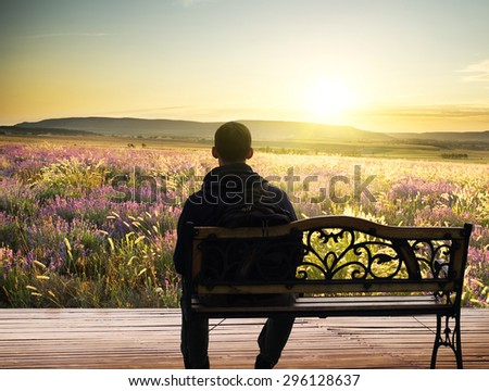 The lonely man sits on a decline.Creative Outdoor Photo. - stock photo