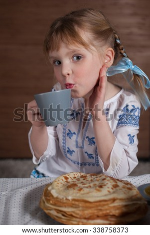 the lovely girl has tea with pancakes   - stock photo