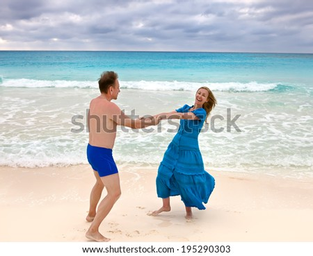 the loving couple is turned on the seashore - stock photo
