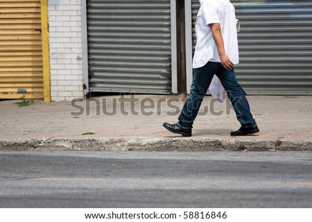 The lower torso of a man walking down the sidewalk along the side of the road. - stock photo