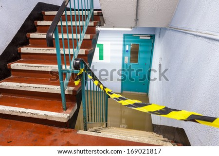 The lowest level of a car parking garage is taped off due to it being flooded. - stock photo