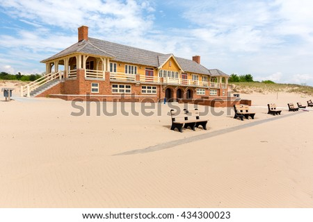 The Ludington State Park Beach House under blue skies and white puffy clouds on a summer day. Rippled beach sand in the foreground - stock photo