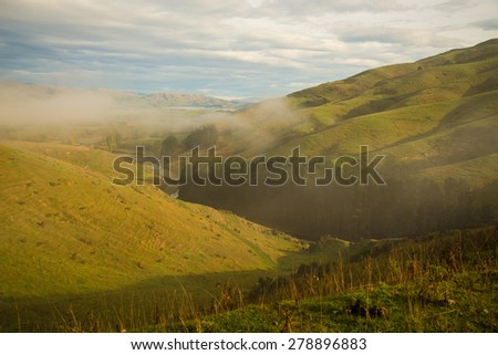 The lush green and scenic farmlands of South Island, New Zealand - stock photo