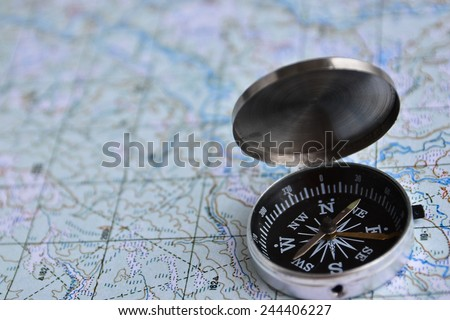 The magnetic compass is located on a topographic map. Equipment for travel - map and compass. - stock photo