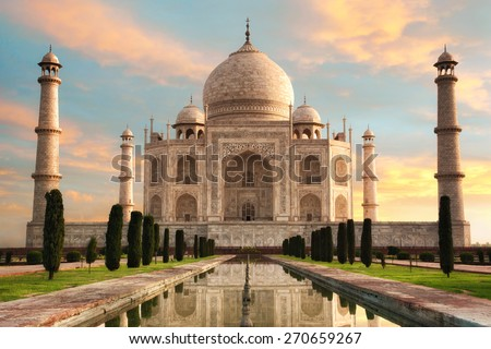 The magnificent Taj Mahal in India shows its full splendor at a glorious sunrise with pastel-colored sky - stock photo