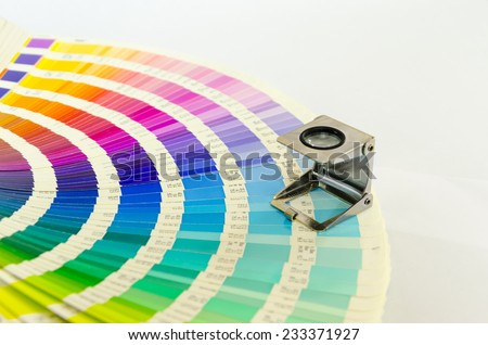 The magnifying glass standing on a color palette print - stock photo