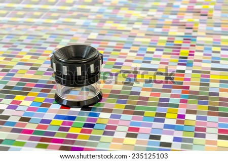 The magnifying glass standing on a leaf of the test print - stock photo