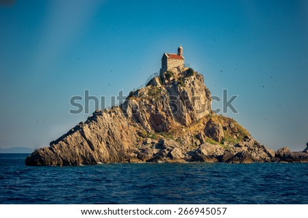 The Mali Katic island with the small church on the top is famous tourist destination and swallows nesting place, Montenegro. - stock photo
