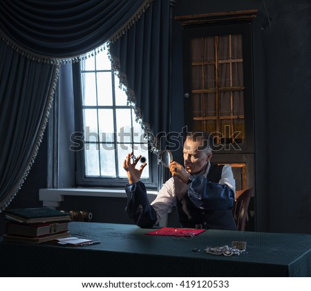 The man - a jeweler in the old workshop exploring the jewels - stock photo