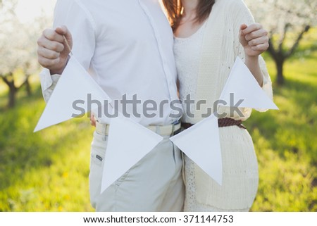 the man and woman standing together. hands of the man and the woman the holding tags on a thread. tags on a thread. - stock photo
