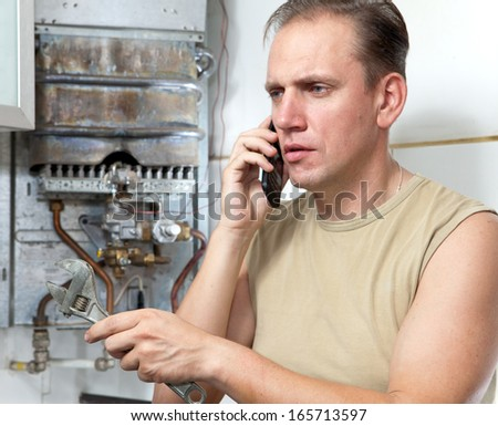 The man calls by phone to cause the repairman of gas water heaters  - stock photo
