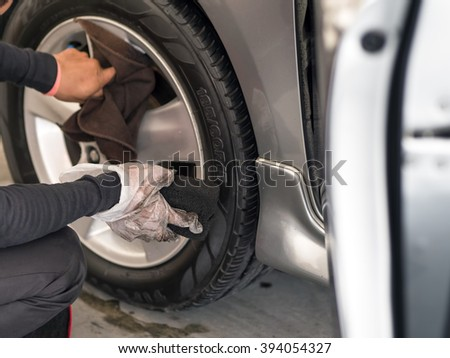 The man cleaning car wheels in a car wash center - stock photo