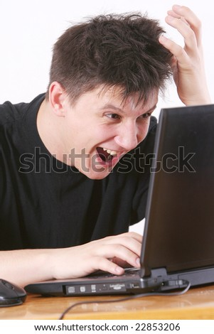 The man in a black vest smiles at work behind the laptop - stock photo