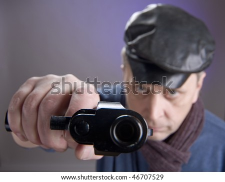 The man in a cap with pistol. Sharpness on hand - stock photo
