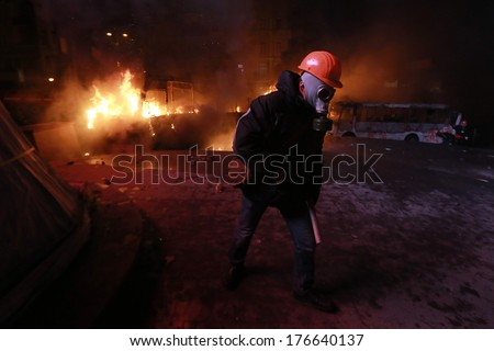 The man in a gas mask on a background of burning buses. Kyiv, Ukraine, January 19, 2014 - stock photo