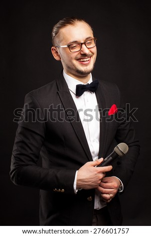 The man in a suit of illusionist-conjurer on red background - stock photo