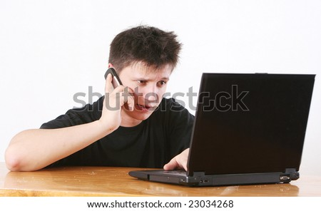 The man in black emotionally works behind the laptop and talks by a mobile phone - stock photo