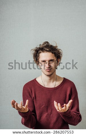 The man in glasses in front of two palms, resteryannost asks something. On a gray background. - stock photo