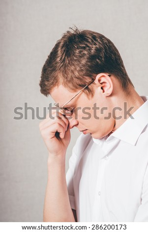 The man in glasses tired sleep. On a gray background. - stock photo