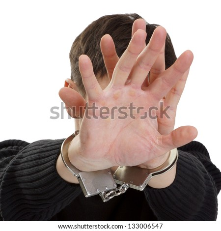 The man in handcuffs closes hands a face. - stock photo