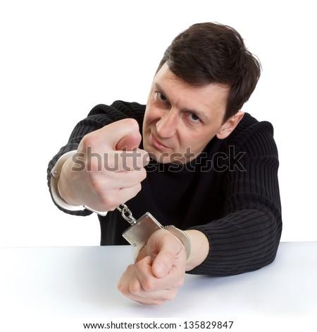 The man in handcuffs shows a fig. - stock photo