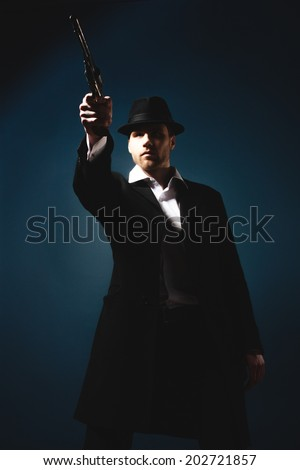 The man in style Chicago gangster with gun on dark background - stock photo