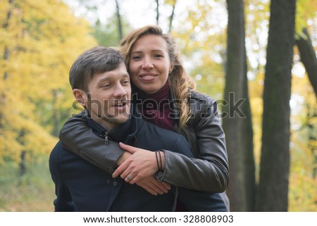 The man in the coat is back, and his young woman hugging and smiling - stock photo