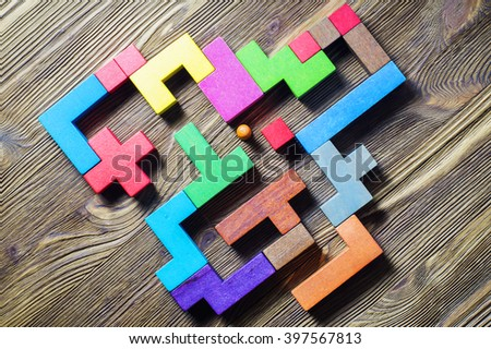 The man in the maze, flat lay. The concept of a business strategy, analytics, search for solutions, the search output. Labyrinth of colorful wooden blocks, tetris, top view. - stock photo