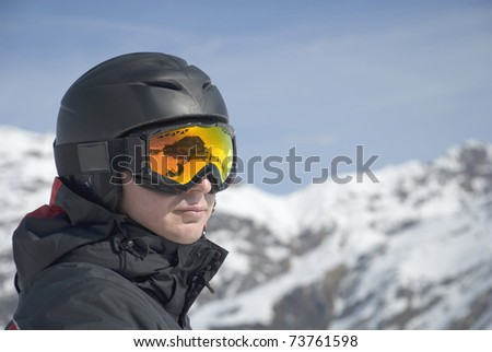 The man in the mountain-skiing form in a helmet and glasses against mountains - stock photo