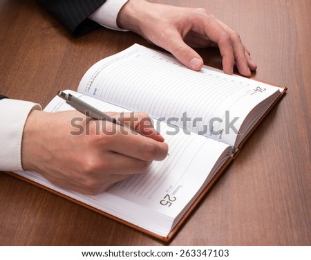The man in the suit writes in the weekly - stock photo
