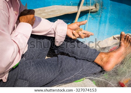 The man is mending nets fishing on the boat in Mui Ne fishing village, Vietnam - stock photo