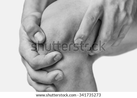 The man is touching the knee joint due to acute pain. Monochrome image, isolated on a white background - stock photo