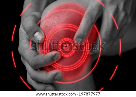 The man is touching the knee joint due to acute pain, pain area of red color - stock photo