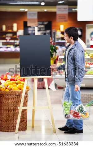 The man looking at an empty board with a basket with meal in shop - stock photo